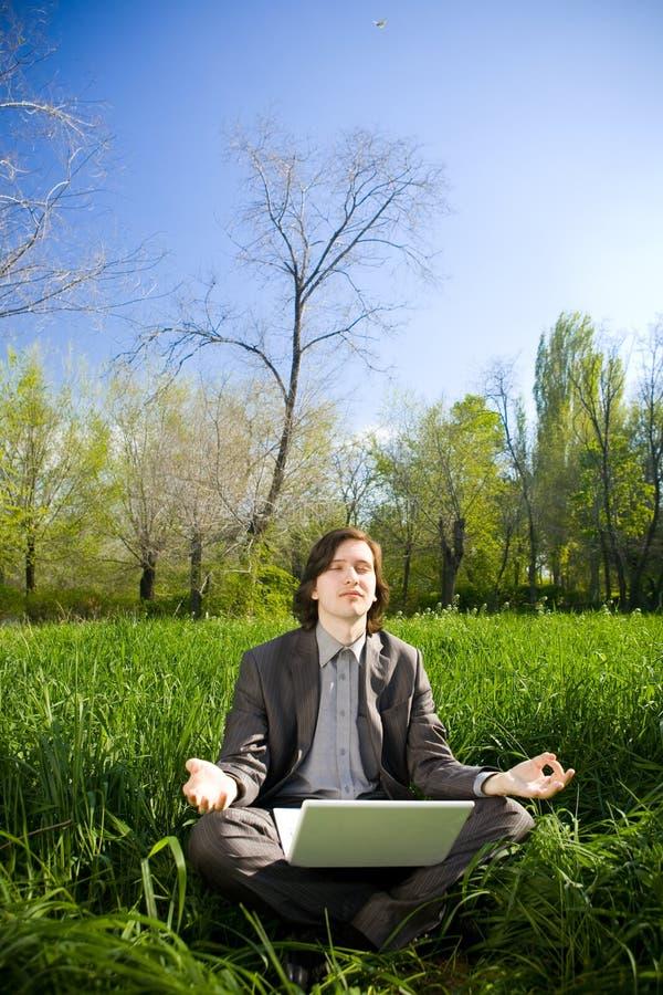 Een bedrijfsmens ontspant op het grasgebied royalty-vrije stock afbeeldingen