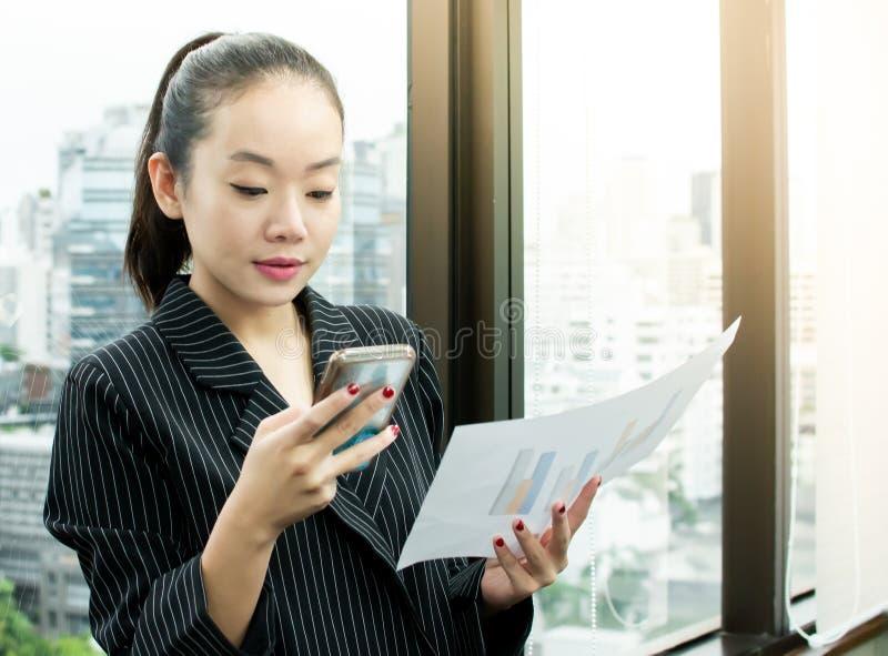 Een bedrijfsvrouw die haar mobiele telefoon voor het werken met behulp van royalty-vrije stock fotografie
