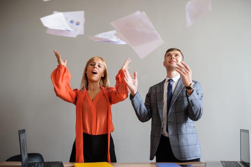 Een bedrijfsvrouw en een man die documenten omhoog werpen stock foto's