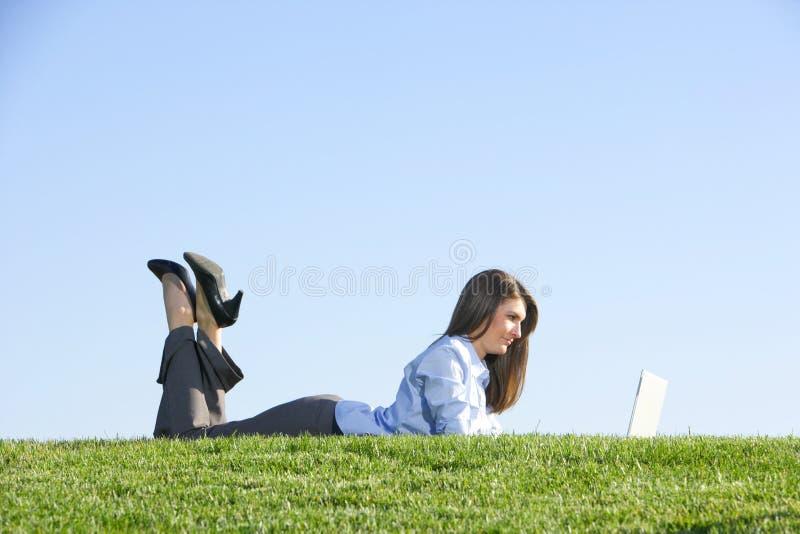 Een bedrijfsvrouw op laptop op een gebied royalty-vrije stock foto