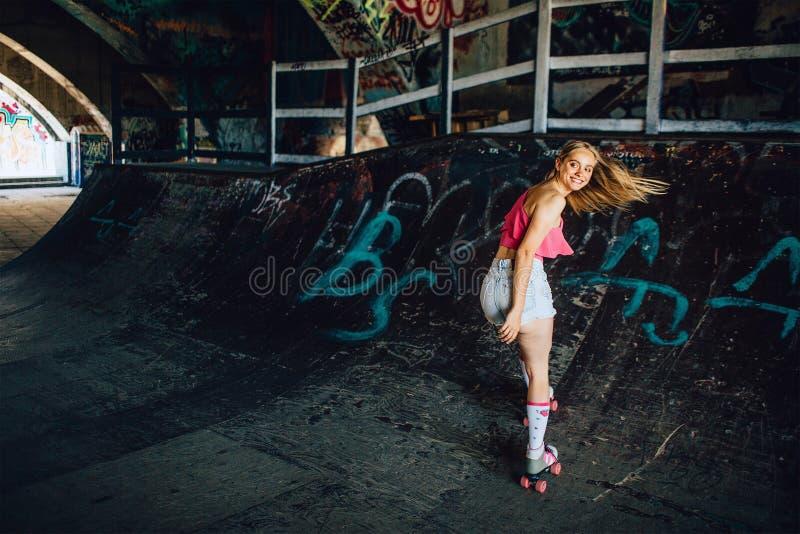 Een beeld die van well-built rollerblaider achteruit berijden Zij kijkt achter zorgvuldig Het meisje glimlacht Haar haar golft royalty-vrije stock foto's
