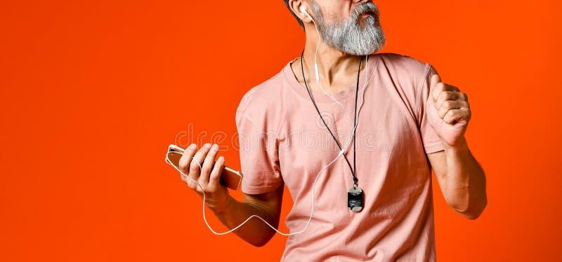 Een beeld van een bejaarde kale hoofdmens die aan muziek met hoofdtelefoons luisteren royalty-vrije stock afbeelding