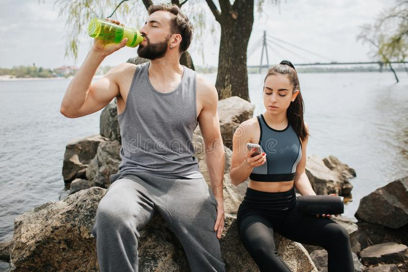 Een beeld van de jonge mens en vrouw sititng samen op een rots Zij hebben één of ander rust Meisje bekijken de telefoon stock foto