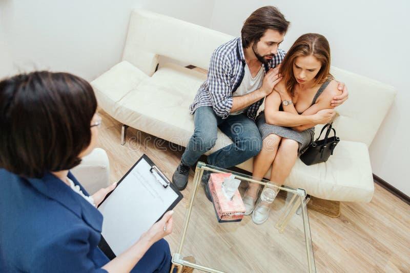 Een beeld van de mens die zijn vrouw koesteren Hij bekijkt haar Het meisje is verstoord Zij kijkt neer aan de vloer De therapeut  stock foto
