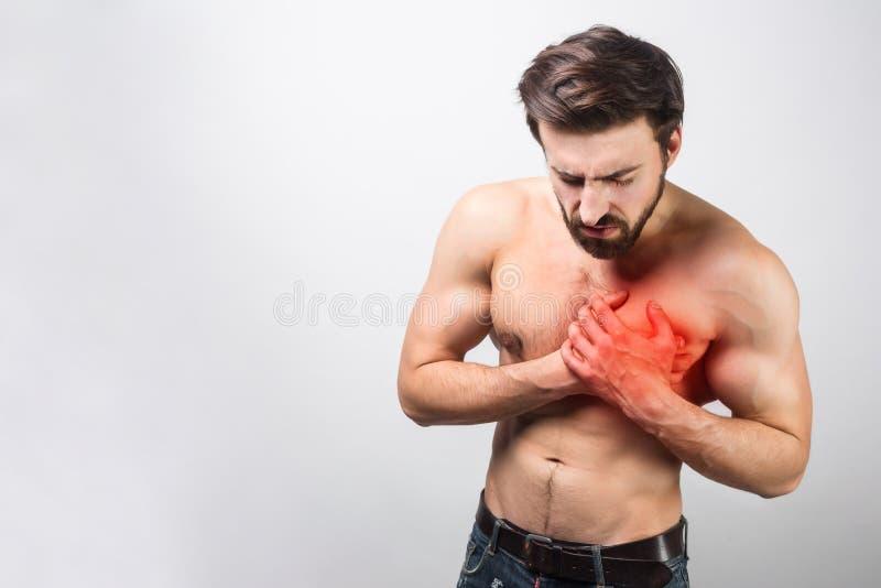 Een beeld van jong en knap hebbend een hartpijn in zijn borst het ` s is vrij ongebruikelijk voor zijn tijd om dit te hebben royalty-vrije stock afbeeldingen
