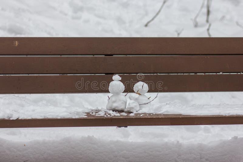 Een beeld van sneeuwman twee op een houten bank royalty-vrije stock foto