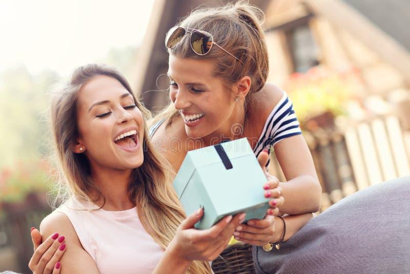 Een beeld van twee meisjesvrienden die een verrassingsverjaardagsgeschenk maken stock afbeeldingen
