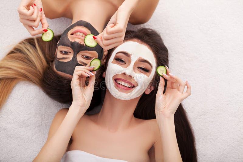 Een beeld van twee meisjesvrienden die met gezichtsmaskers op ove ontspannen royalty-vrije stock foto