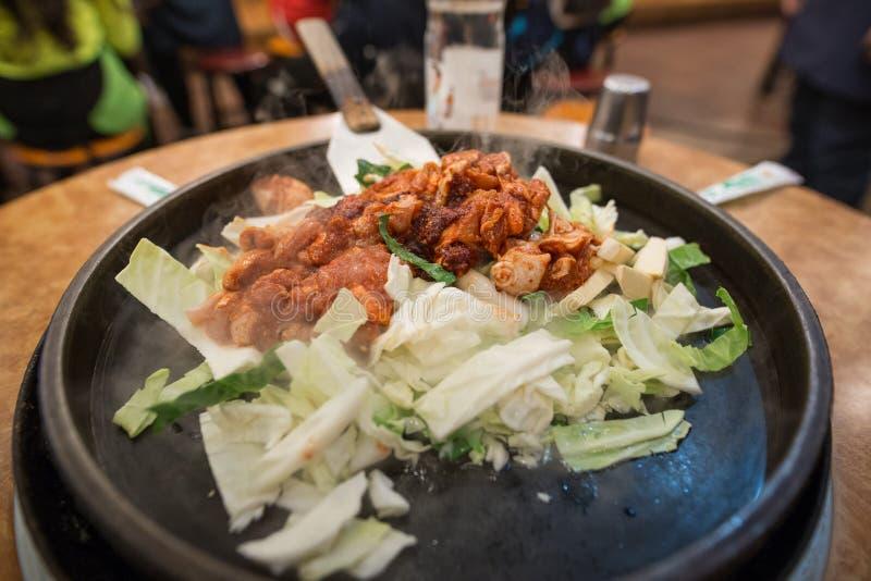 Een beeld van vlees met groenten in een zwarte pan wordt gekookt die royalty-vrije stock fotografie