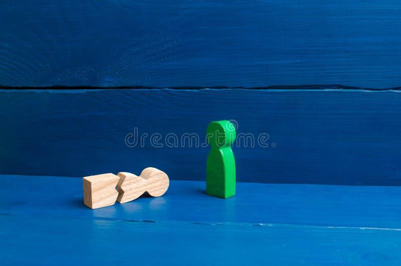 Een beeldje van een groene mens bevindt zich over een gevallen gespleten mens Het concept wederzijdse hulp, eerste hulp Sociale b stock fotografie