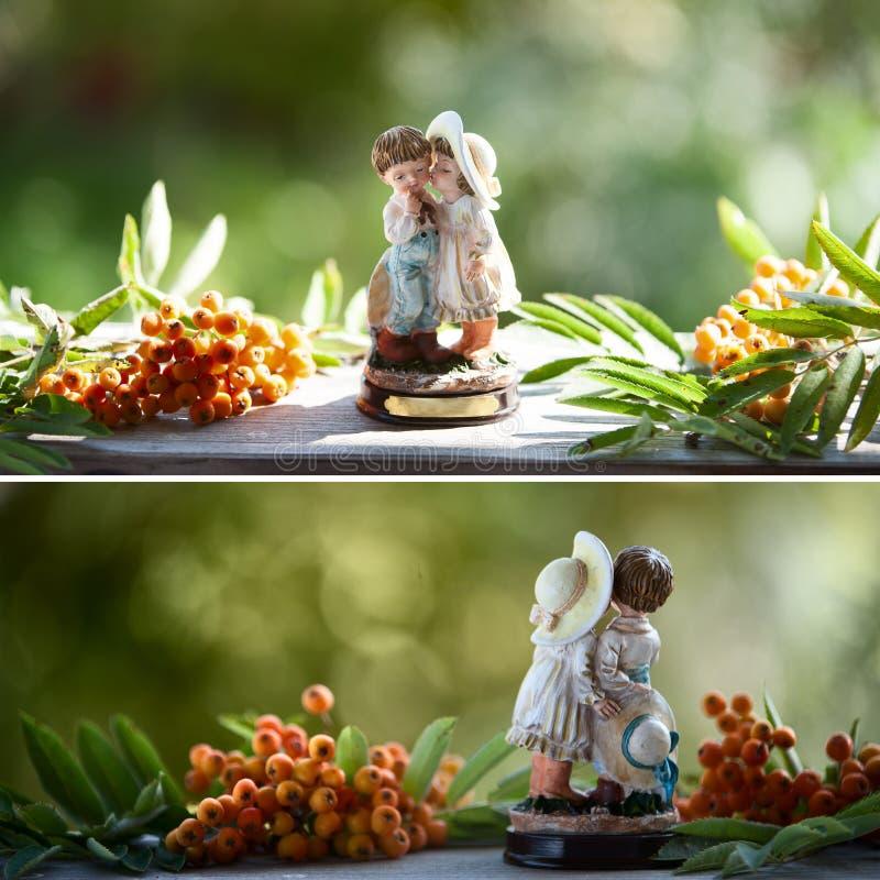 Een beeldje van een jongen en een meisje op een natuurlijke groene achtergrond, lijsterbessenbessen royalty-vrije stock afbeelding