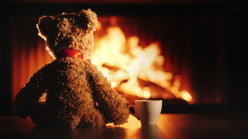 Een beerwelp met een kop thee zit tegenover de open haard Comfort en warmte in het huis stock afbeelding