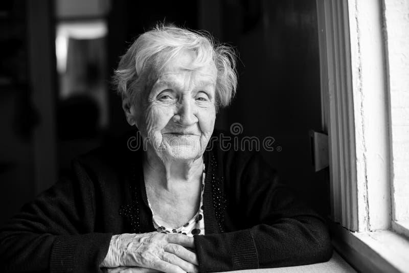 Een bejaard gelukkig vrouwen zwart-wit portret stock foto's