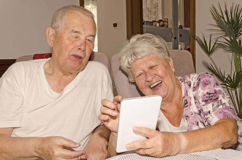 Een bejaard paar geniet van Internet op de tablet royalty-vrije stock foto's