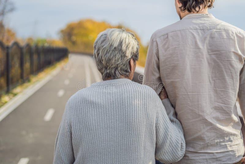 Een bejaard paar loopt in het park met een mannelijke hulp of volwassen kleinzoon Gevend voor de bejaarden, het aanmelden zich stock foto