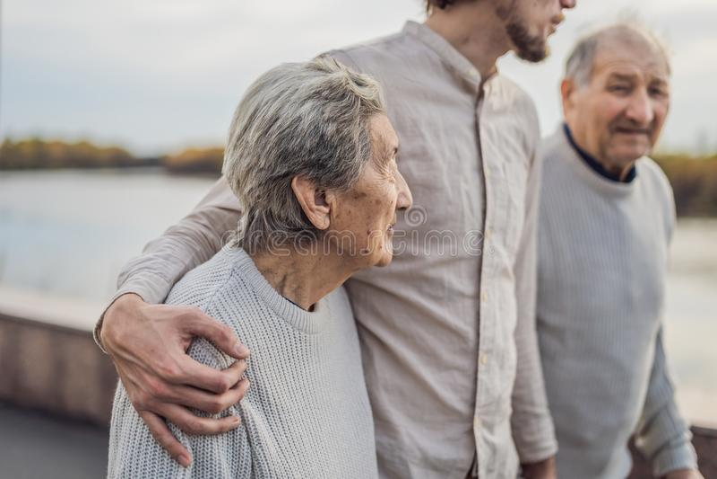 Een bejaard paar loopt in het park met een mannelijke hulp of volwassen kleinzoon Gevend voor de bejaarden, het aanmelden zich royalty-vrije stock afbeeldingen