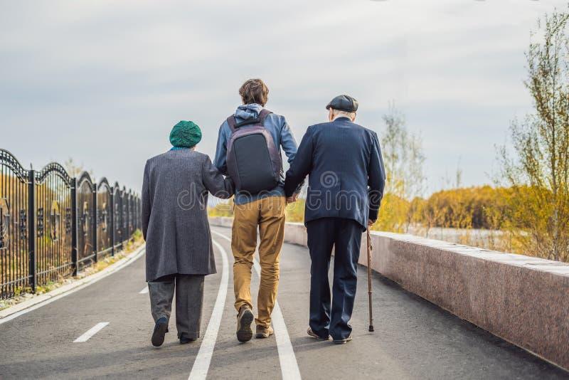 Een bejaard paar loopt in het park met een mannelijke hulp of volwassen kleinzoon Gevend voor de bejaarden, het aanmelden zich stock foto's