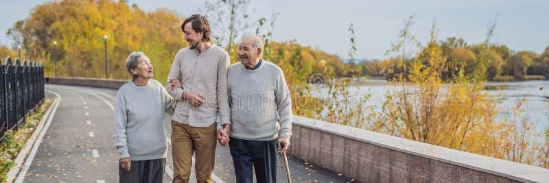 Een bejaard paar loopt in het park met een mannelijke hulp of volwassen kleinzoon Gevend voor de bejaarden, die BANNER aanmelden  royalty-vrije stock fotografie
