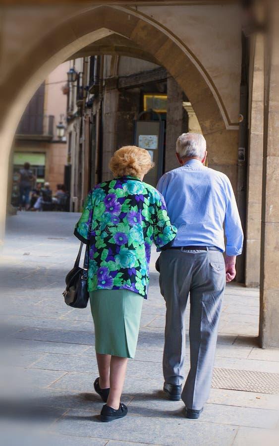 Een bejaard paar van gepensioneerden die onderaan de stadsstraat wandelen stock fotografie