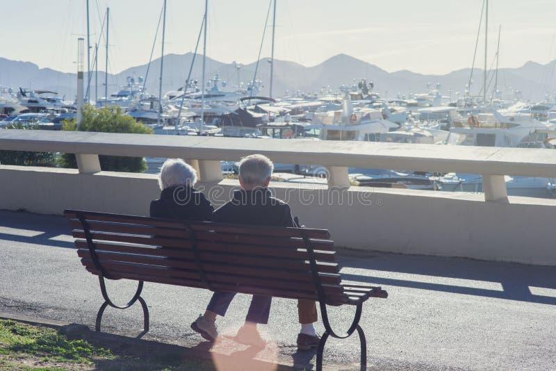 Een bejaard paar zit op een bank onder witte dure jachten en bergen op een zonnige dag royalty-vrije stock foto