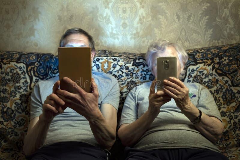 Een bejaard paar zit op de laag met gadgets, bekijkt dicht hen hun gezichten stock foto