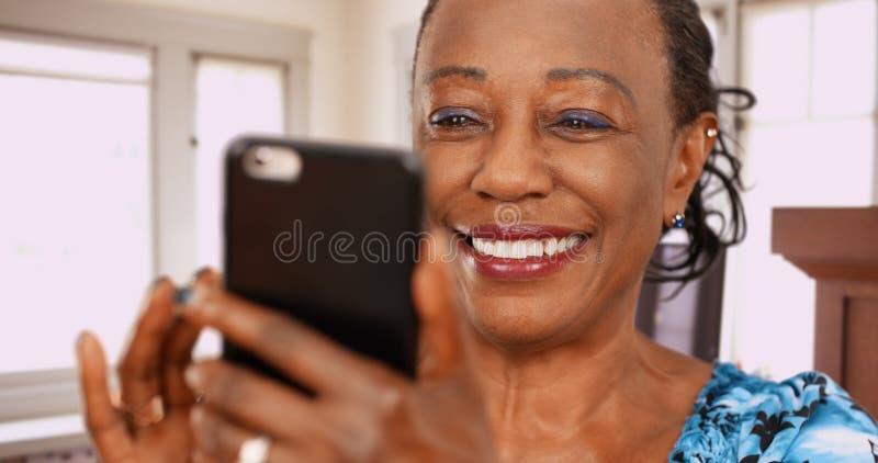 Een bejaarde achtervrouw jat bij haar het favoriete dateren app stock foto