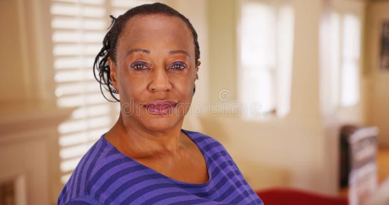 Een bejaarde Afrikaanse Amerikaanse vrouw stelt voor een portret in haar huis stock afbeelding