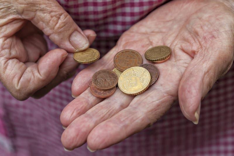 Een bejaarde dame houdt een paar centen van euro royalty-vrije stock afbeelding