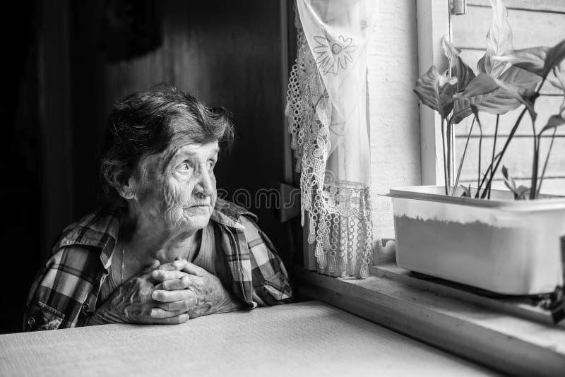 Een bejaarde dame zit droevig dichtbij het venster van zijn oud huis royalty-vrije stock afbeeldingen