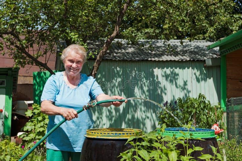 Een bejaarde in de tuin met water stock afbeeldingen