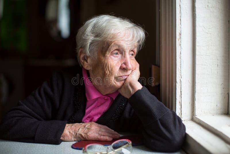 Een bejaarde die droevig uit het venster kijken stock afbeelding
