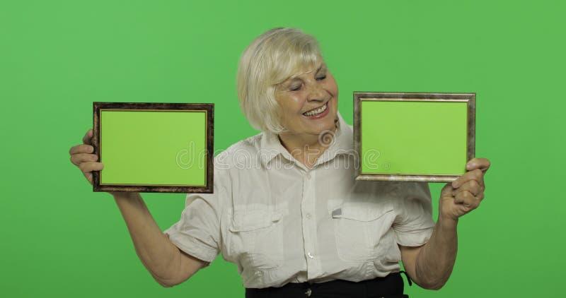 Een bejaarde die twee kaders met groen beeld houden grootmoeder Twee in: 1 royalty-vrije stock foto's