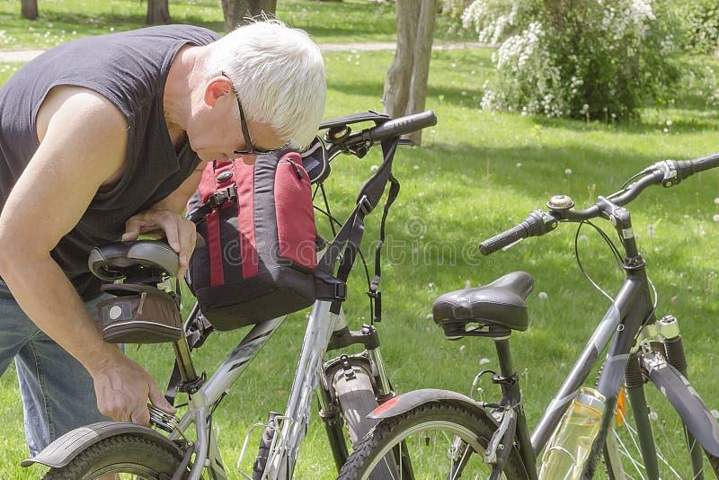 Een bejaarde die in zonnebril een fiets in het Park herstellen royalty-vrije stock afbeelding
