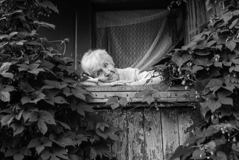 Een bejaarde droevige vrouw in de portiek onder de struiken stock afbeelding