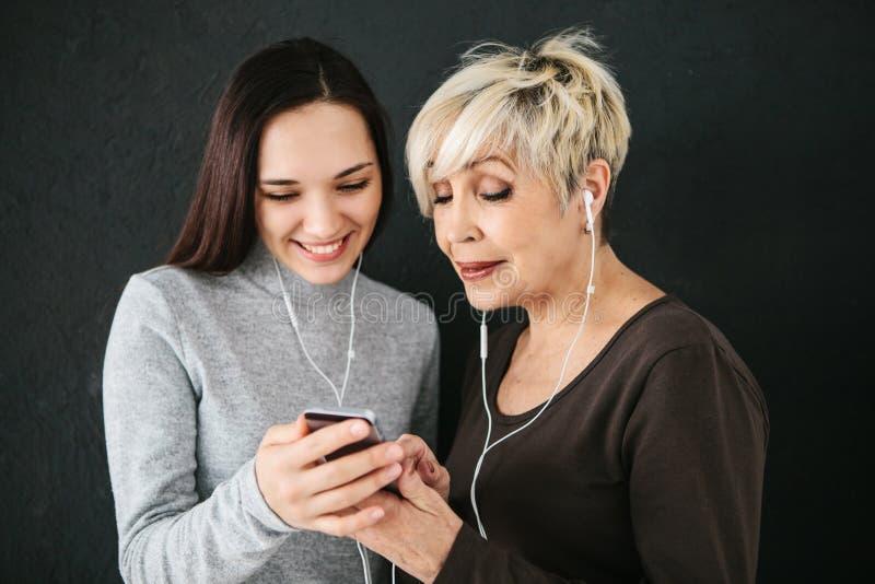 Een bejaarde en een jong meisje luisteren samen aan muziek Communicatie tussen mensen van verschillende generaties stock afbeeldingen