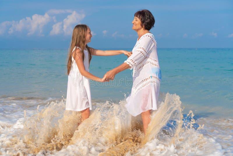 Een bejaarde en een mooi meisje op het strand De holdingshanden van de grootmoederkleindochter op de achtergrond van de golven va stock foto's