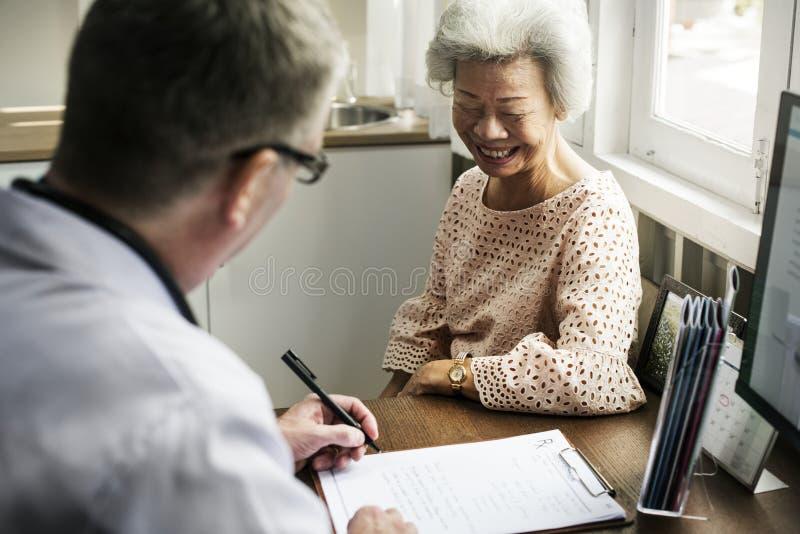 Een bejaarde geduldige vergadering arts bij het ziekenhuis royalty-vrije stock afbeelding