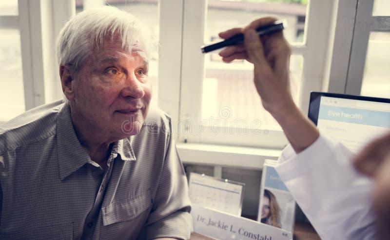 Een bejaarde geduldige vergadering arts bij het ziekenhuis stock fotografie