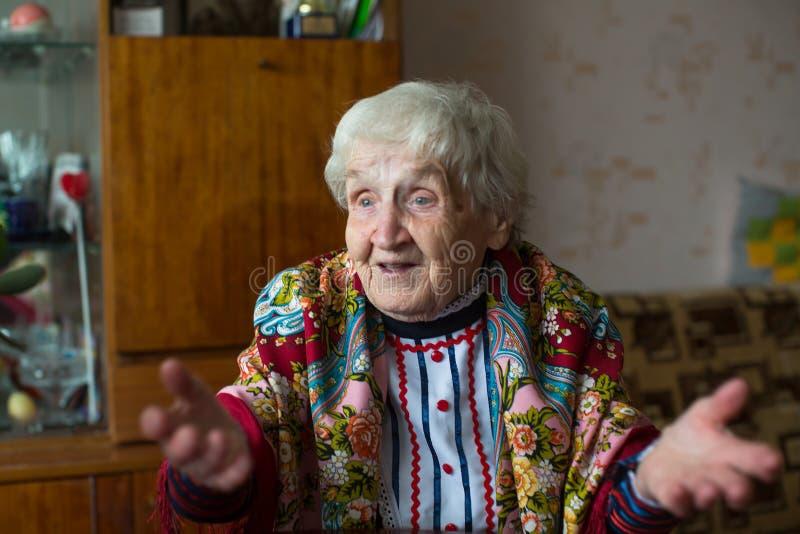 Een bejaarde gelukkige vrouw in heldere kleren en een sjaalgebaren royalty-vrije stock foto