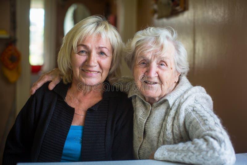 Een bejaarde gelukkige vrouw met haar volwassen dochter stock fotografie