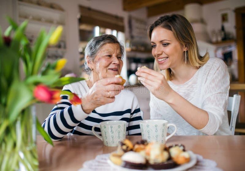 Een bejaarde grootmoeder met een volwassen kleindochterzitting bij de lijst die thuis, cakes eten royalty-vrije stock afbeelding