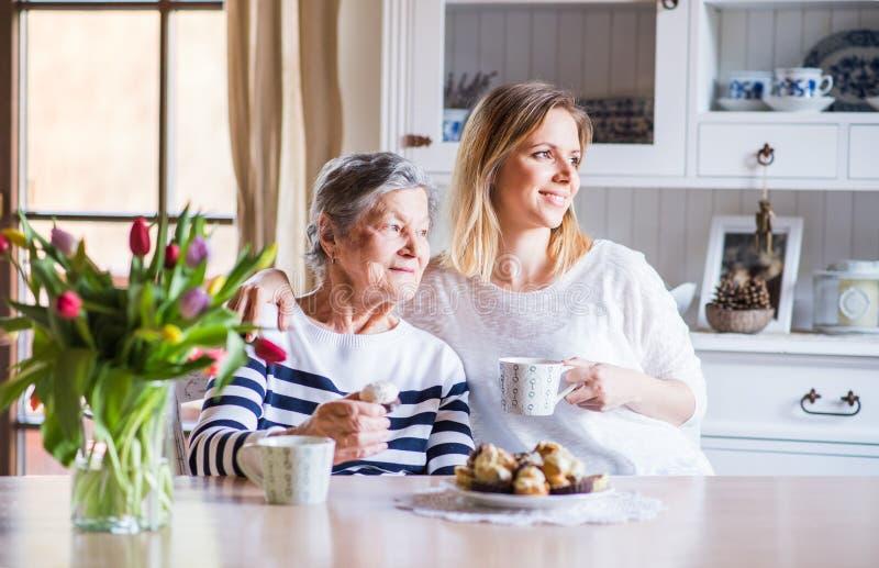 Een bejaarde grootmoeder met een volwassen kleindochterzitting bij de lijst thuis royalty-vrije stock fotografie