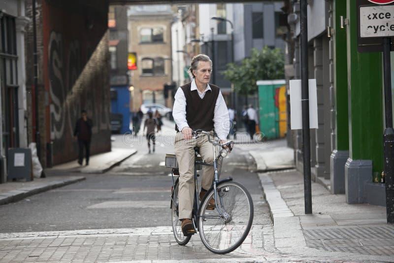 Een bejaarde heer in een vest op een fiets, zet de hoofdweg aan royalty-vrije stock afbeeldingen