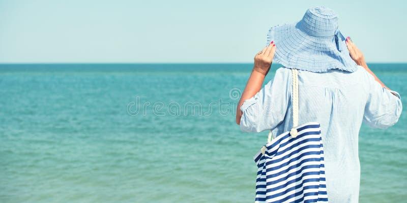 Een bejaarde in een hoed bekijkt het overzees De vakantie van de zomer stock fotografie