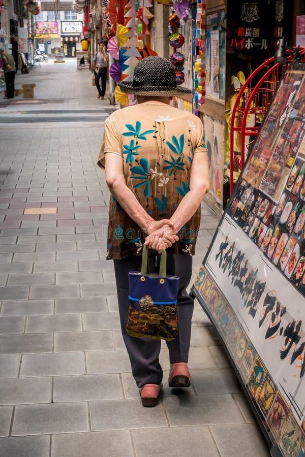 Een bejaarde in een hoed en met een zak die onderaan de straat lopen stock afbeelding