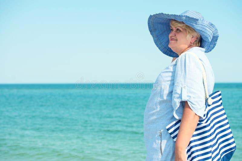 Een bejaarde in een hoedenrust op het overzees De vakantie van de zomer stock foto's