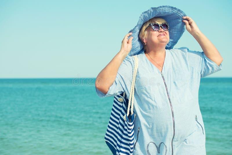Een bejaarde in een hoedenrust op het overzees De vakantie van de zomer stock foto