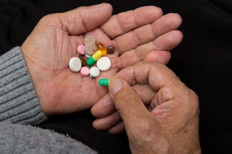 Een bejaarde houdt heel wat gekleurde pillen in oude handen op een donkere achtergrond Identificatie van pillen, het leren die, e royalty-vrije stock foto