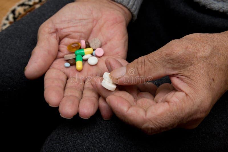 Een bejaarde houdt heel wat gekleurde pillen in oude handen Pijnlijke oude dag Gezondheidszorg van oudere mensen royalty-vrije stock afbeeldingen