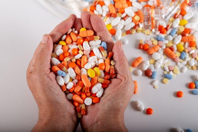 Een bejaarde houdt veel gekleurde pillen in handen op een witte achtergrond royalty-vrije stock fotografie